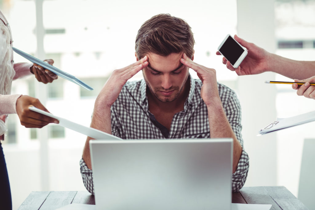 Man holding head in distress at desk. If you're tired of the stress of the world around you, talk with an anxiety therapist in Illinois. Here you will be supported with CBT for anxiety and a listening ear. Begin anxiety treatment in Riverside, Il when you're ready!