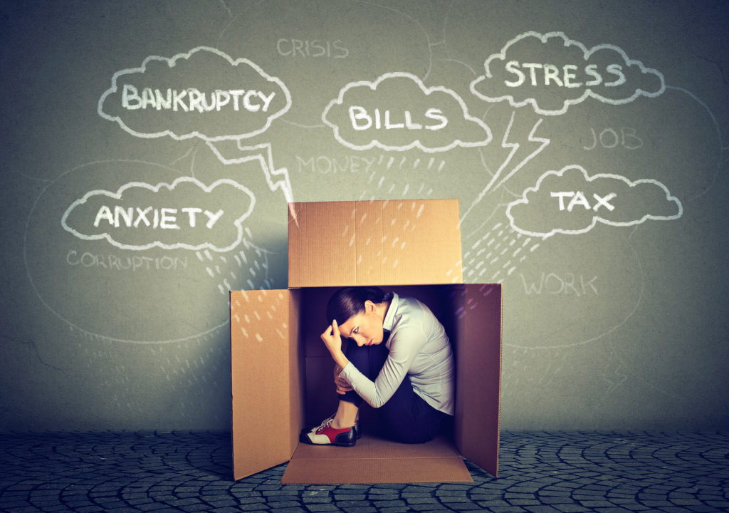 Person crouched in a box distress about responsibilities. If you're tired of feeling overwhelmed, an anxiety therapist or a health anxiety therapist can support you. Call now and begin therapy for anxiety. You do not have to continue on, begin anxiety treatment in Riverside, Berwyn, Champaign, or Chicago, soon!
