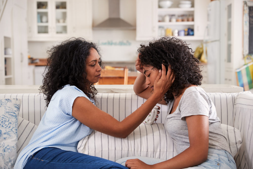 Mom holding daughters face while sitting on couch. Being a part does not come with a manual. Get support with counseling for parents in riverside, or counseling for co-parents here with us!