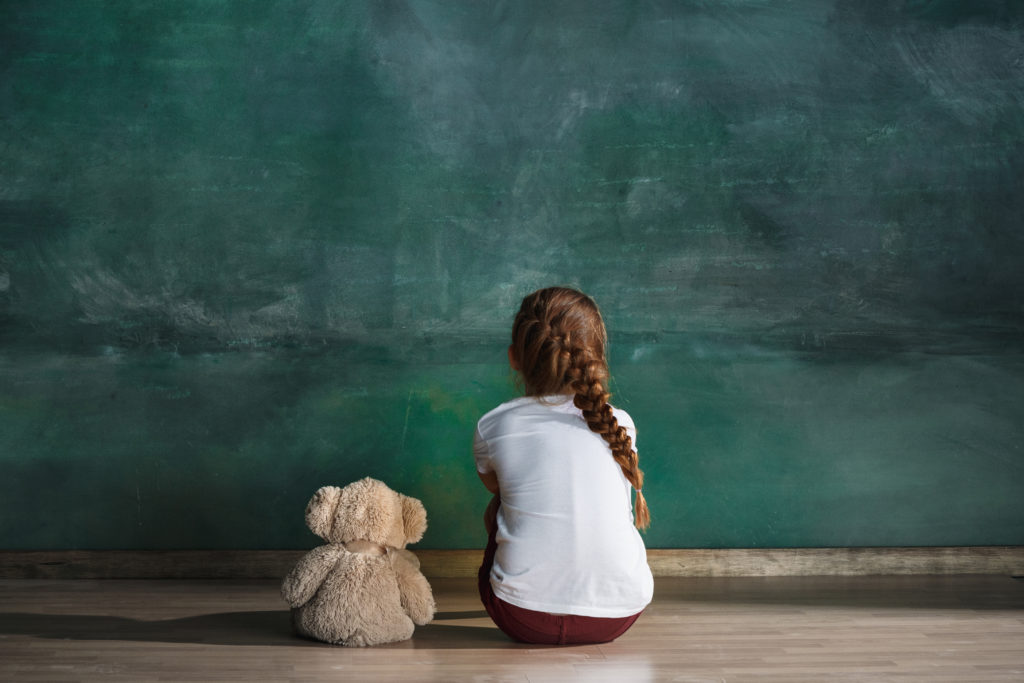 Young girl sitting next to teddy bear facing green wall. Supporting your kids can be complicated, whether you're an overwhelmed mom, or a single parent, we can help you. Try counseling for parents in Riverside, IL or counseling for co-parents today!