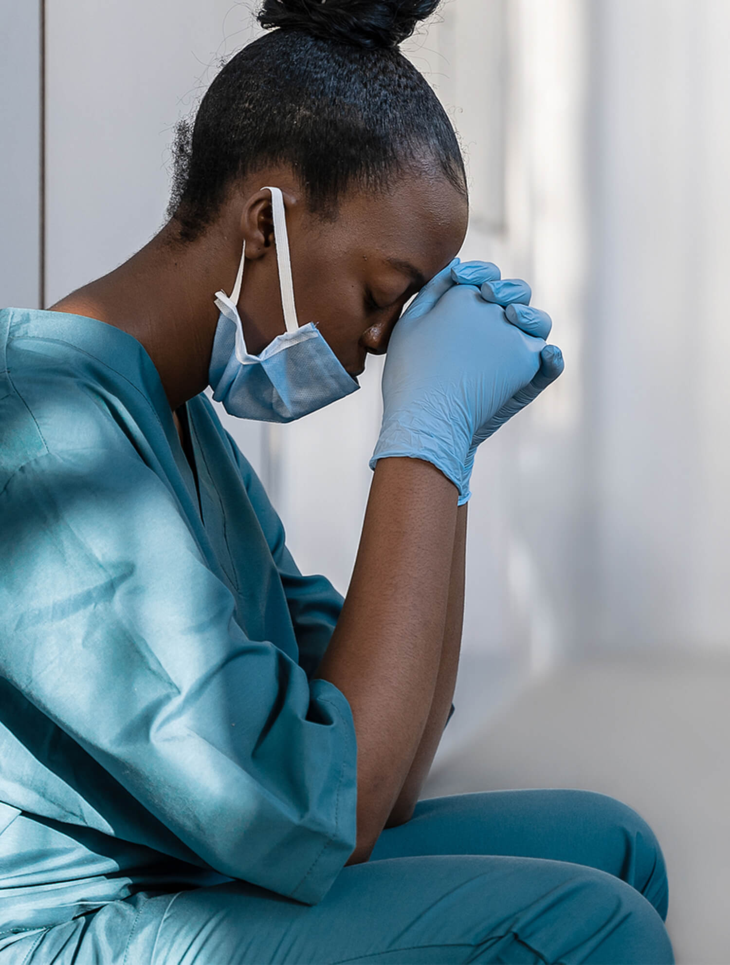 Black doctor in blue scrubs looking down in distress. Working with a stress therapist can help you manage motherhood, work, and school. Consider how cbt for stress can assist you today. Begin stress therapy in Riverside, Berwyn, Forest Park, and Chicago soon for guidance.