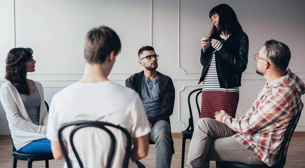 """Woman in support group standing up and speaking. If you're ready to get substance abuse help in Riverside, IL then contact us. Our therapists and addictions counselors are here to support your journey. Search for substance abuse counseling near me """"Western Springs 60558"""" and begin to find freedom here."""