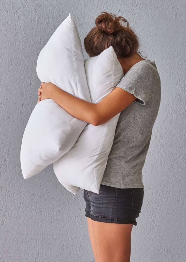 Mom standing against grey background holding white pillows. Being a mom is challenging, so if you're feeling like an overwhelmed mom in Riverside, Il you're not alone. Whether its mom burnout or mom guilt, we can help you.